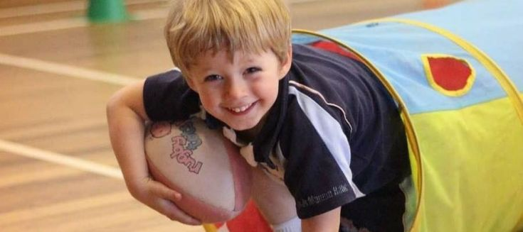 Young boy coming out of a play tunnel with a rugby ball.