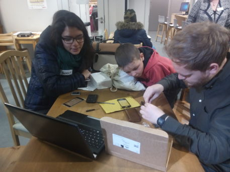 Image of one person fixing a computer while a young woman and young boy look on.