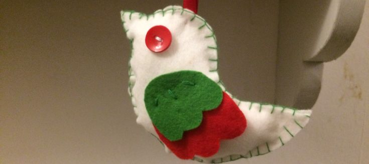 A fabric bird with a red button for an eye.