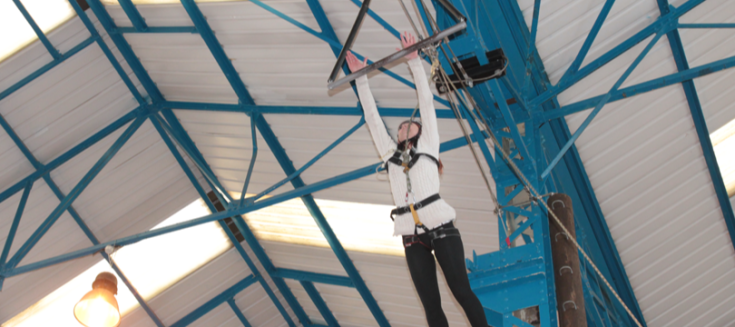 Woman on climbing equipment in the air
