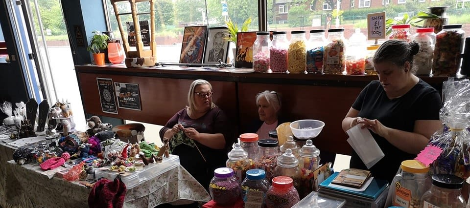 A group of women sat at an arts and crafts stall