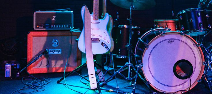 A speaker, guitar and drum set