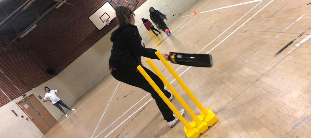 Women playing cricket indoors