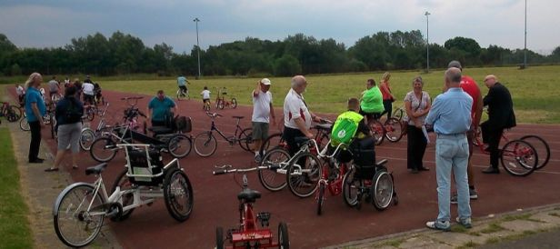 A group of people cycling at a velodrome.