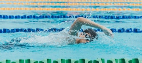 Boy swimming in swimming lane