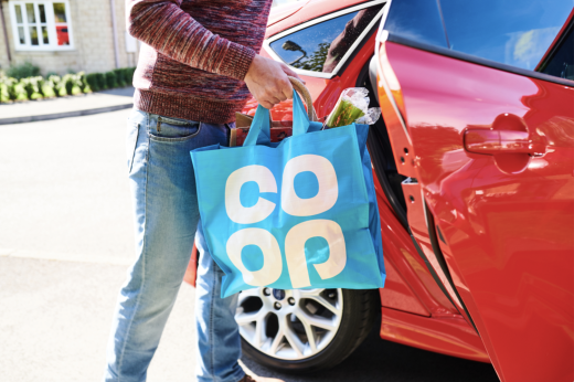 Man outside red car with Co-op shopping bag full of shopping