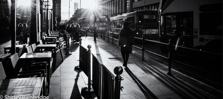 A black and white photograph of a lady walking towards the sun in a busy street