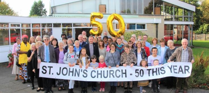 People from the church holding a banner to celebrate 50 years of the church
