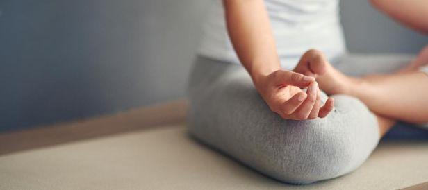 A person meditating with their hands and feet at the centre of focus.