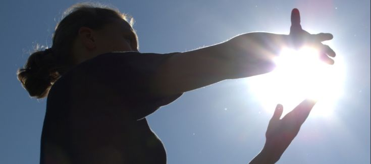 A person performing Tai Chi under the sun.