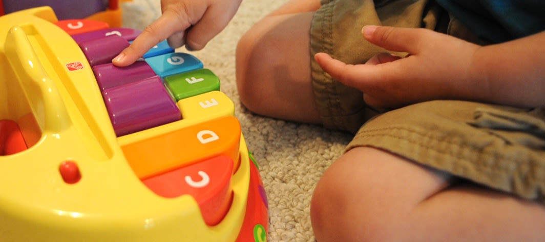 A child playing with an alphabet toy