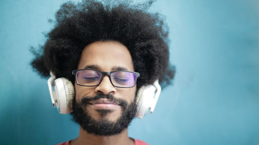 Man in red crew neck shirt with glasses wearing headphones