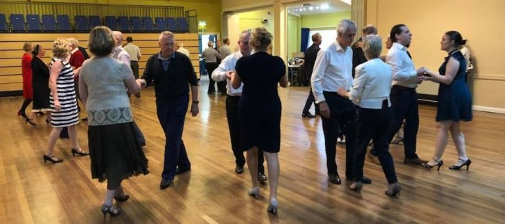 People ballroom dancing in a civic hall