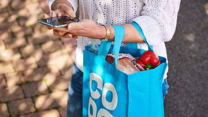 Woman holding her phone and a Co-op shopping bag with food in
