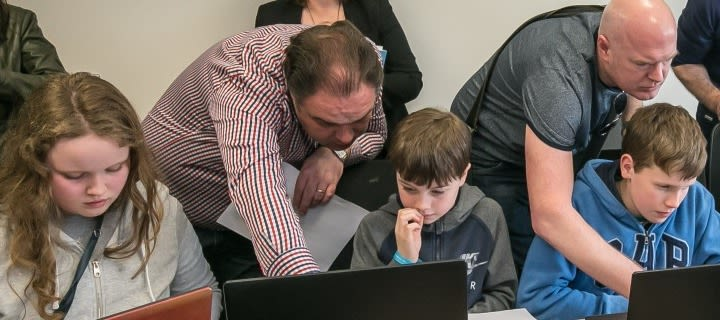 Children sat at computers with adults helping them input information.
