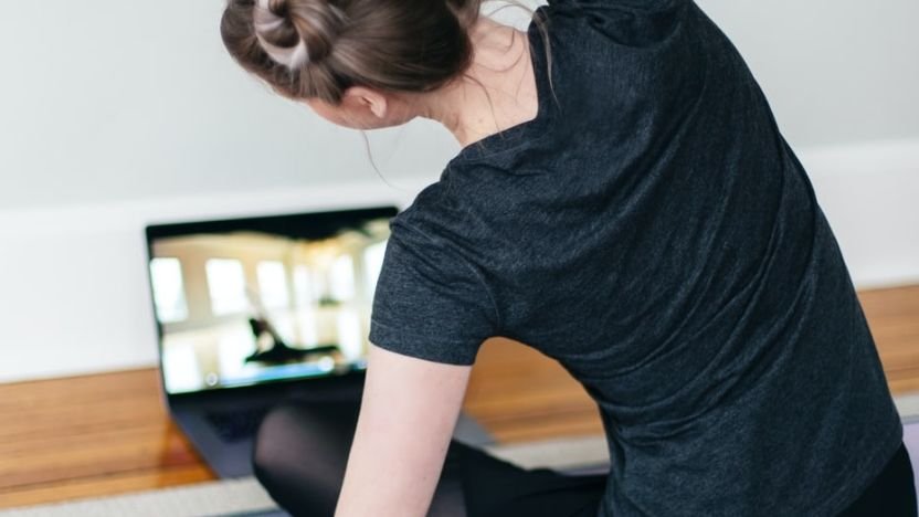 Woman on the floor doing an exercise while watching an online fitness class on a laptop