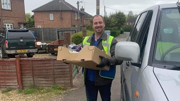 A man holding a cardboard box wearing a high visability vest.