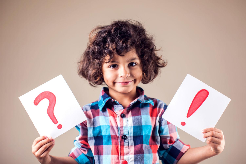 Kind mit Frage- und Ausrufezeichen in den Händen