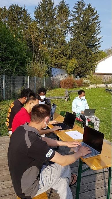 Laptops mit Nutzern in München draußen bei Sonnenschein