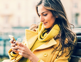 Woman in yellow coat checking her Twitter