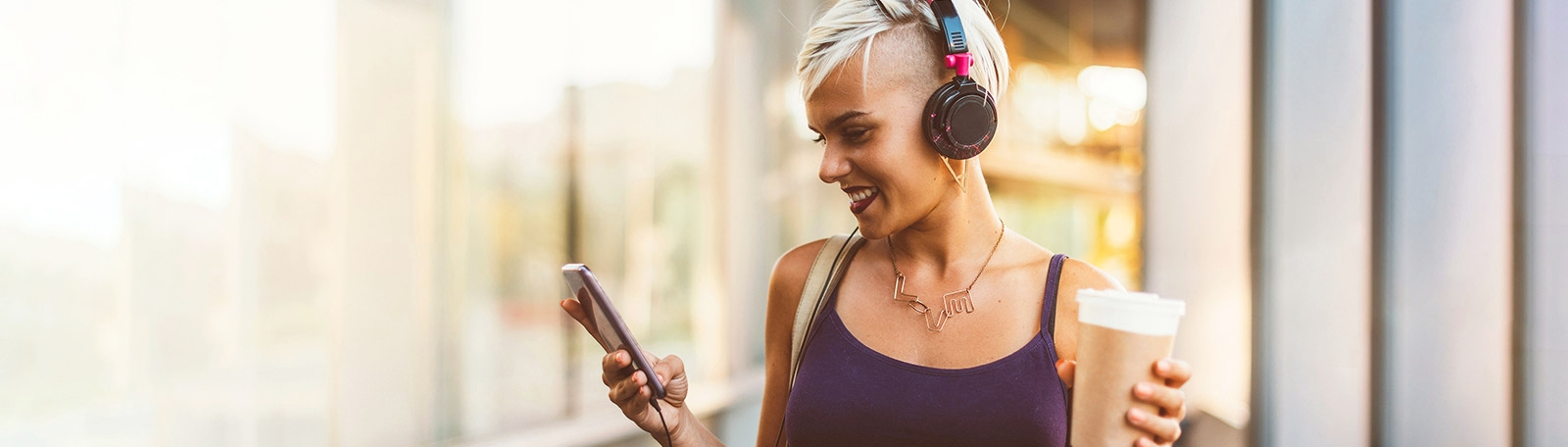 Pretty woman with short blonde hair and headphones checking her phone messages