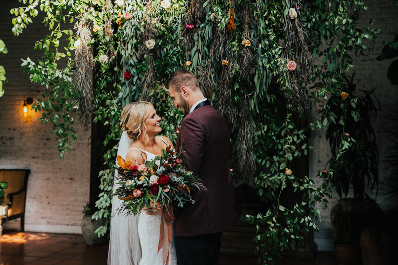 white bride and groom in front of flower wall , bride holding a bouquet