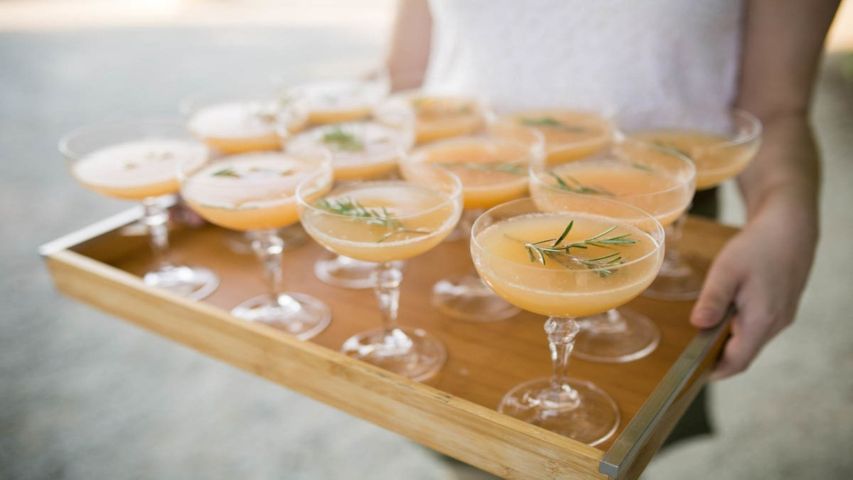 a tray of glasses containing orange colored refreshing summer cocktail