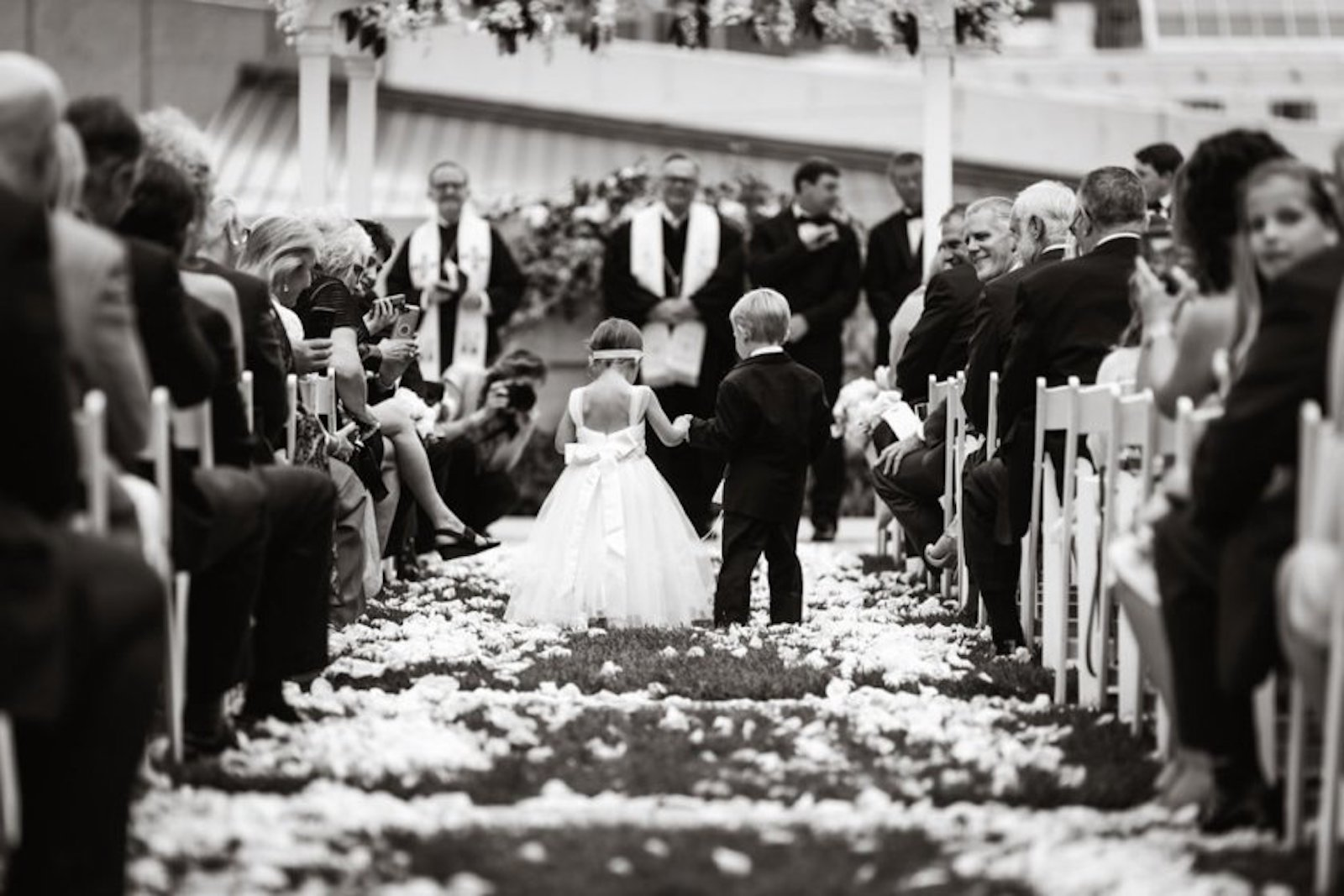flower girl and ring bearer walking down flower covered aisle at wedding
