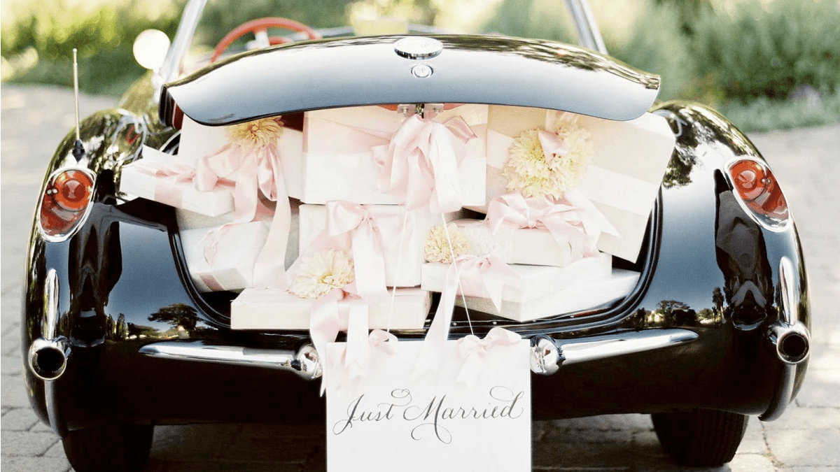 back view of black wedding car with open trunk loaded with wedding gifts and just married written on it