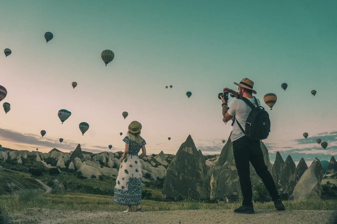 Photographer snapping photos of woman and hot air balloons