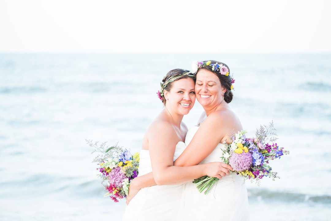 brides celebrate their wedding on the beach before honeymoon