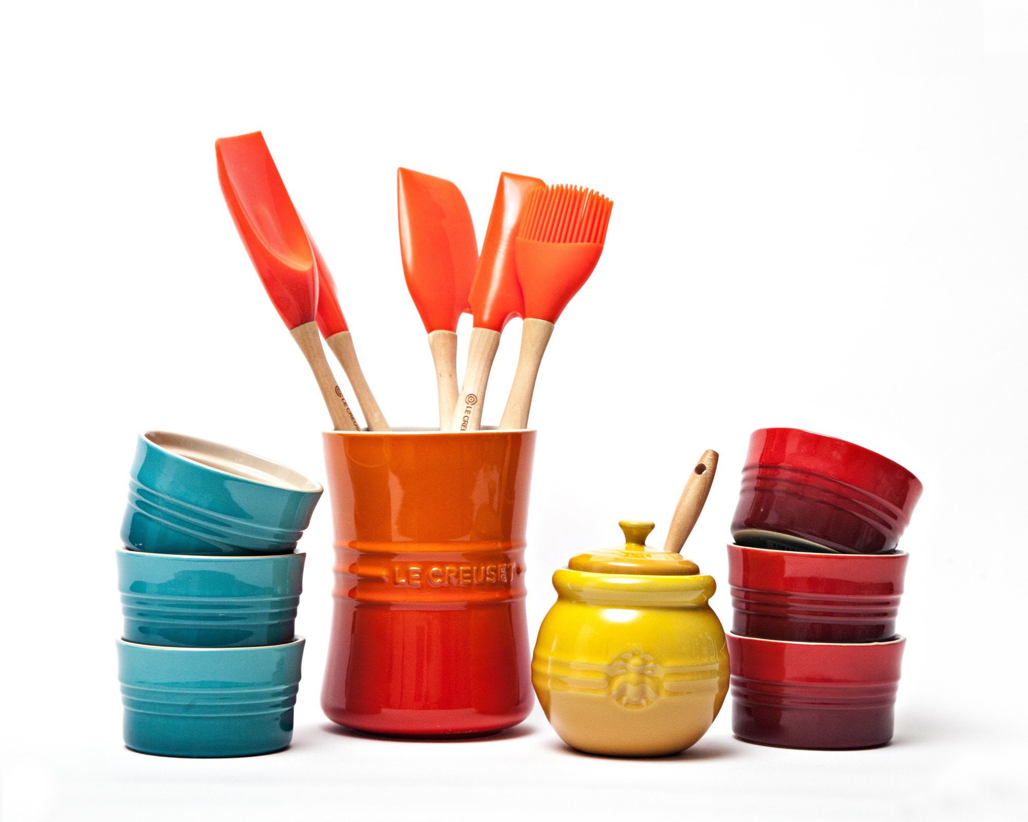 Le Creuset crock with cooking utsensils in flame orange, ramekins in teal blue and red, and honey pot in yellow