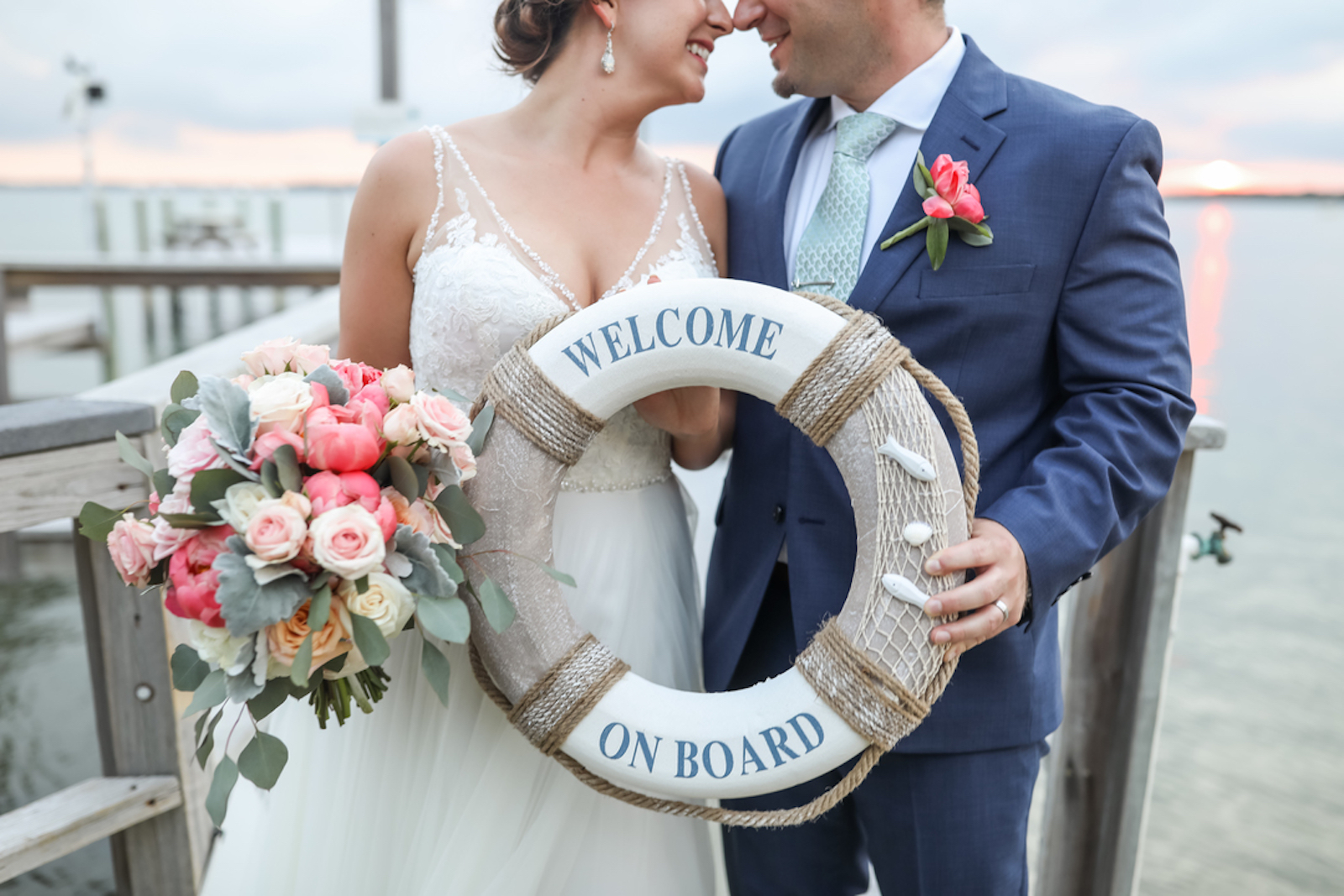 "bride and groom standing on a pier holding up a life preserver that says ""welcome on board"" with pink flowers"
