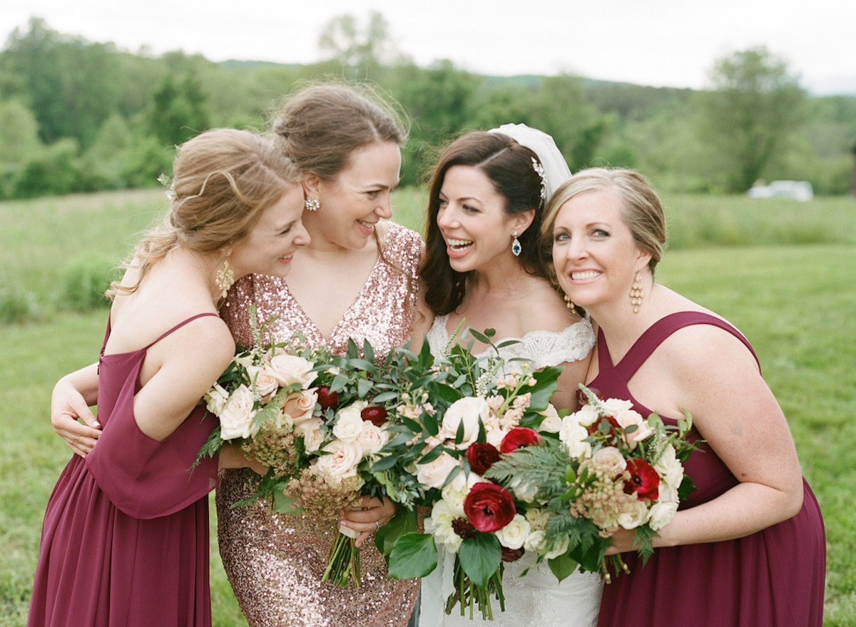 bride and Maid of Honor smiling looking at each other holding bouquet