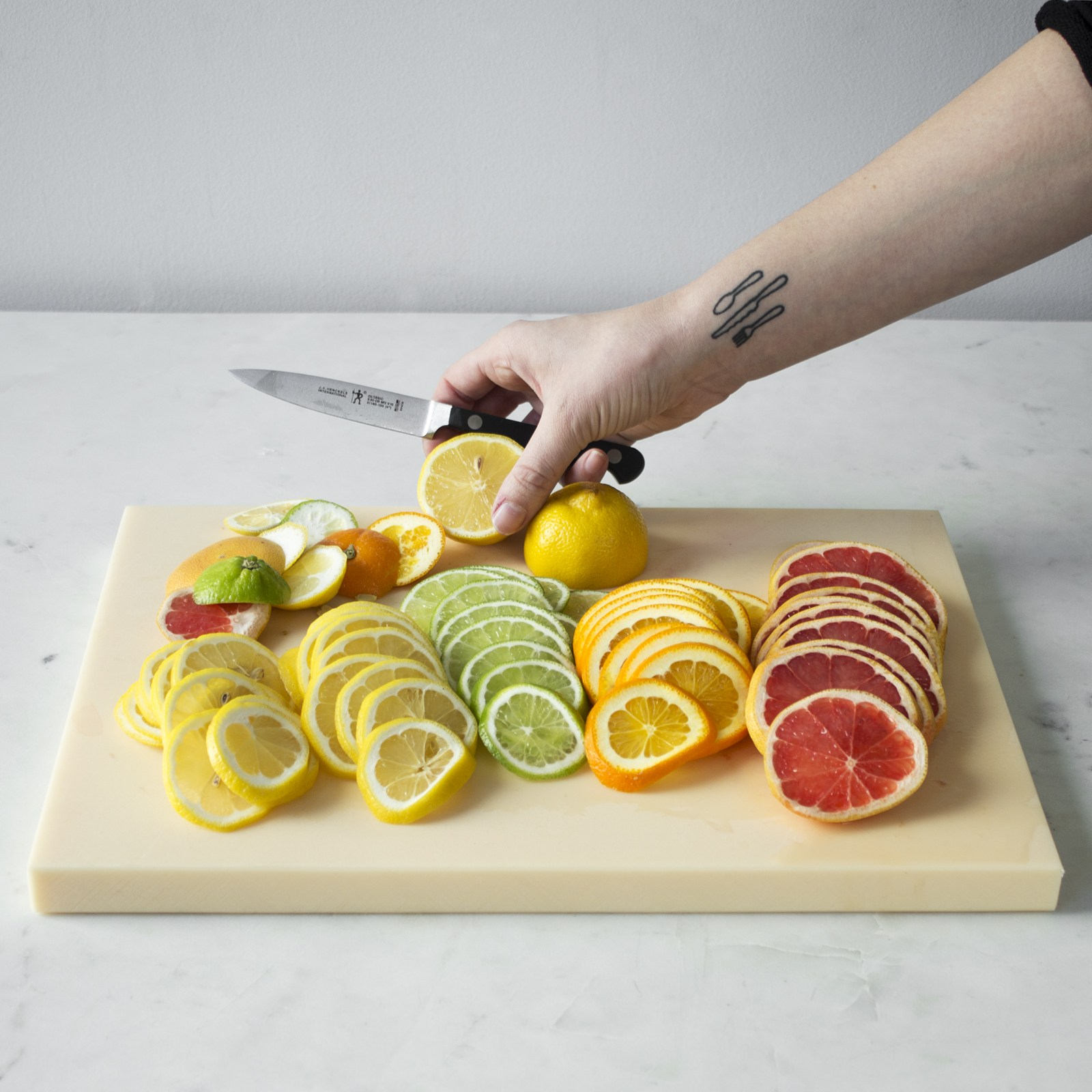 a hand holding a knife and placing lemon on cutting board with yellow, green,orange,red sliced citrus fruits
