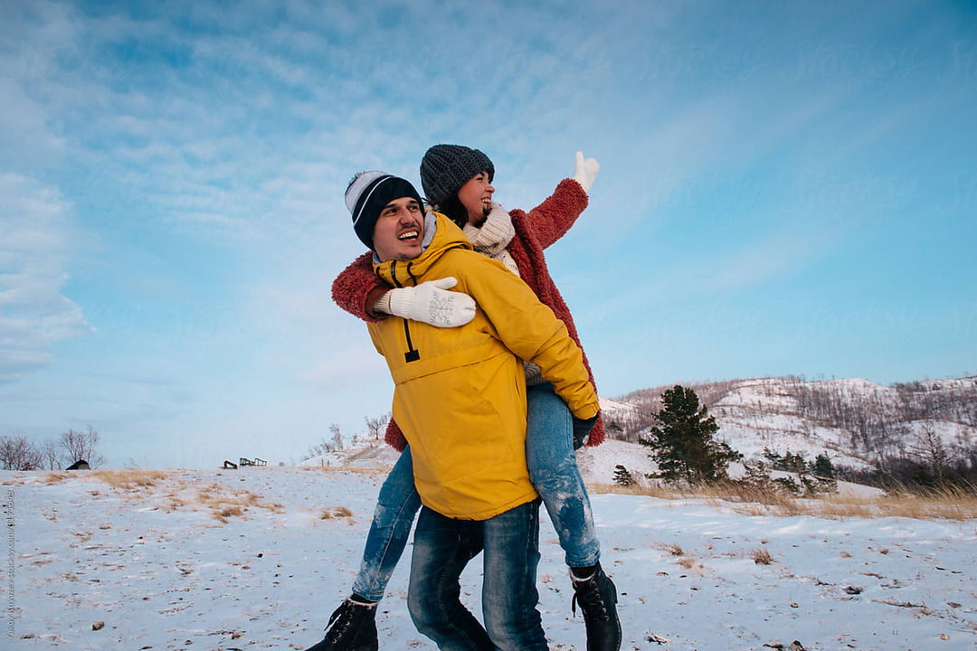Couple piggybacking in snowy mountains