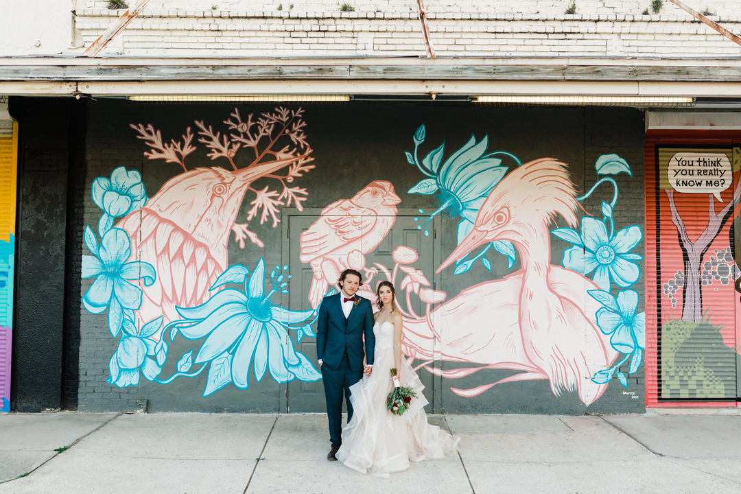 couple poses by graphic wall after wedding