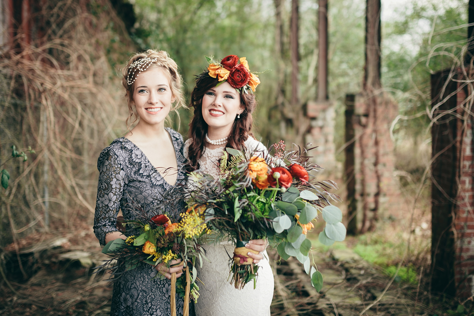 bride and maid of honor with bouquets of orange roses, red ranunculus, and greenery