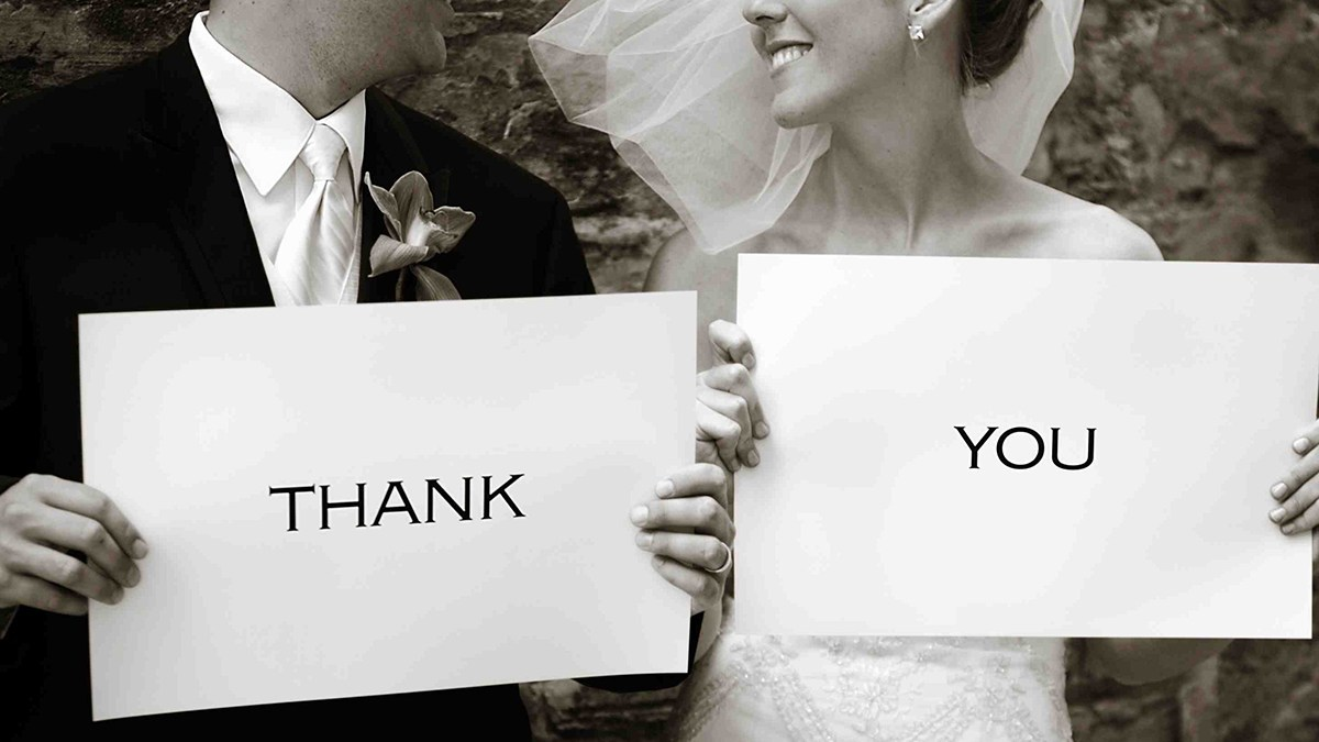 Groom holding white card with Thank  and bride holding card written You