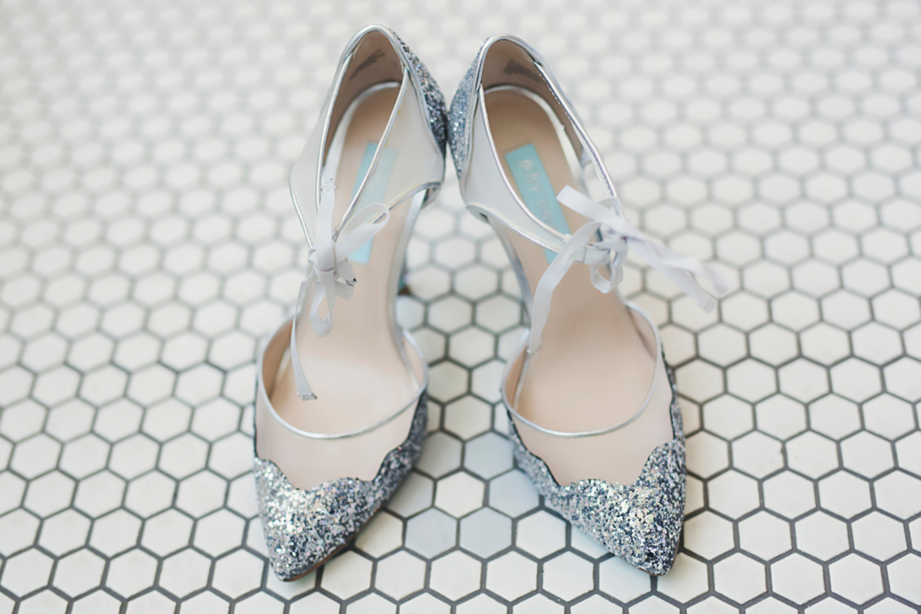 pair of silver glittery high heels with mesh ties on a white and gray tiled floor