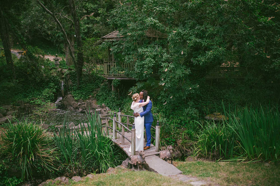 Couple kissing on footbridge over late