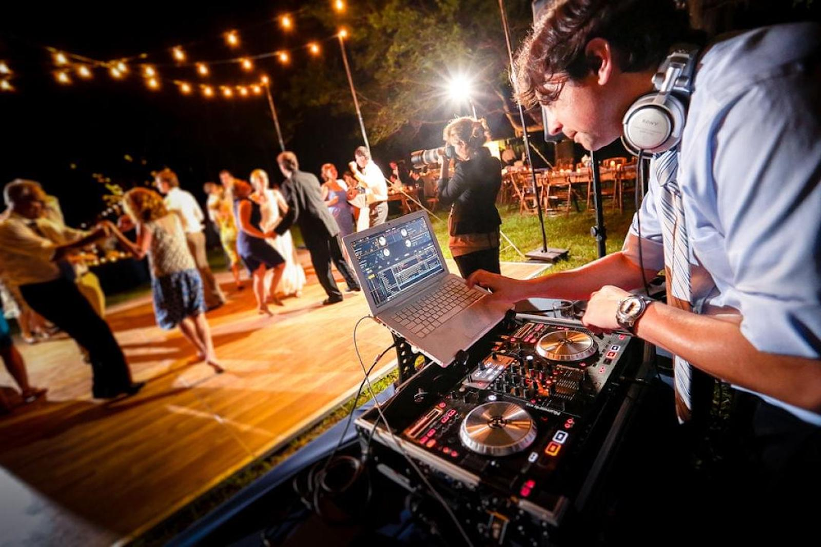 Wedding DJ playing music at an outdoor evening wedding reception