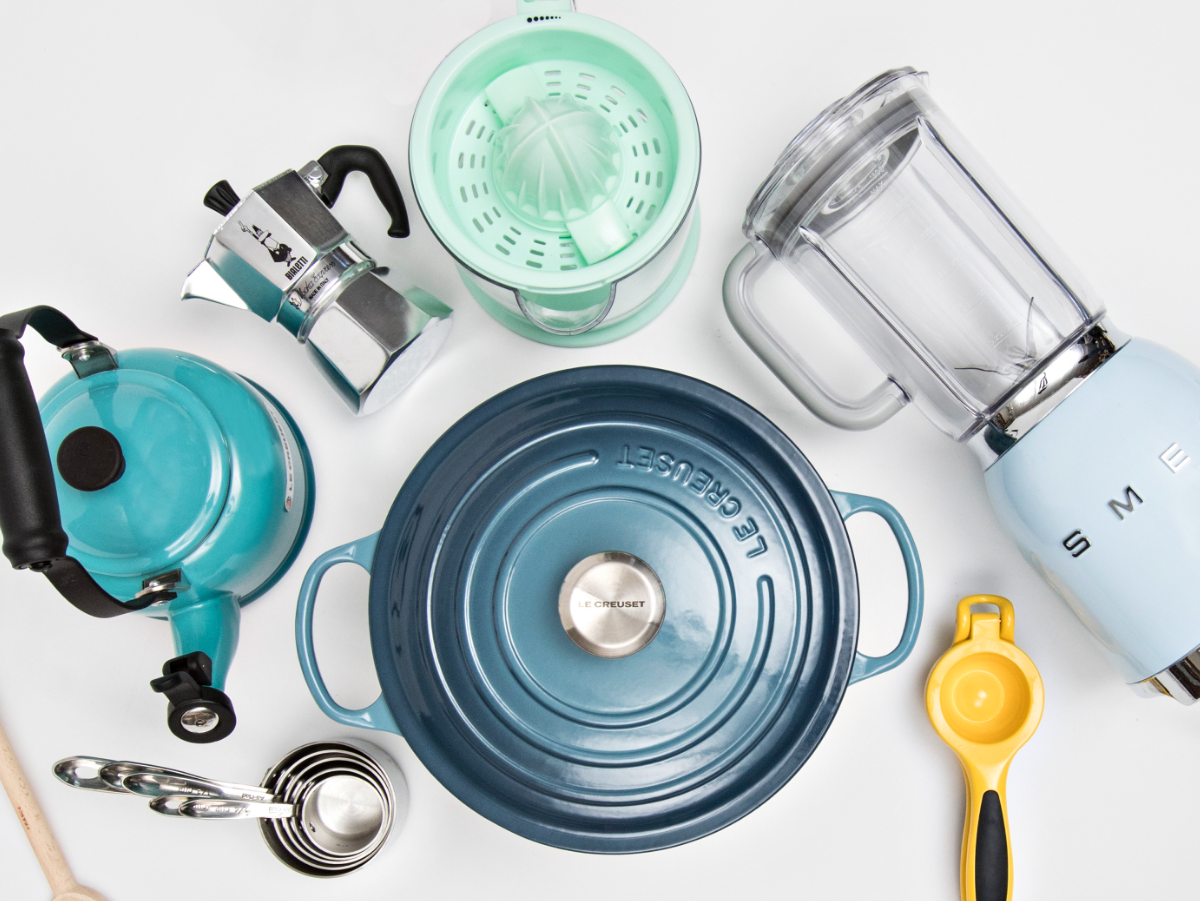 wedding registry gift essentials including a blue Le Creuseut dutch oven, measuring spoons, a yellow citrus juice, and a turquoise citrus juicer
