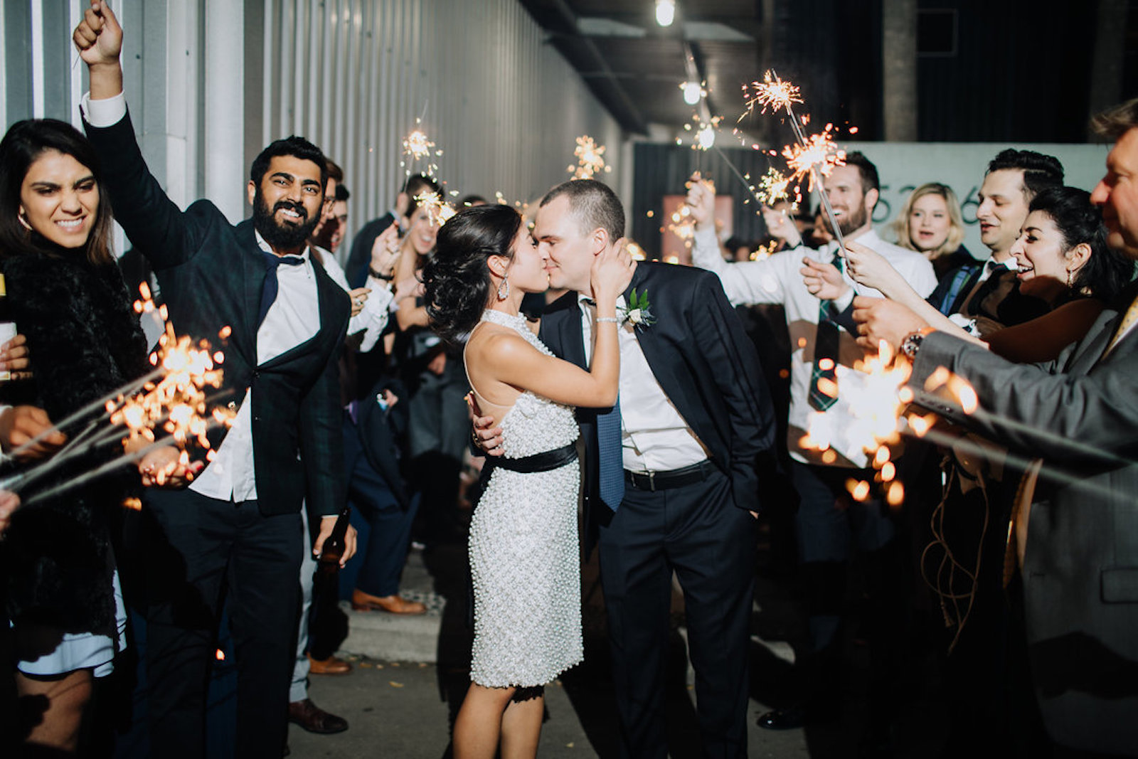 bride and groom kissing with guests cheering and holding sparklers