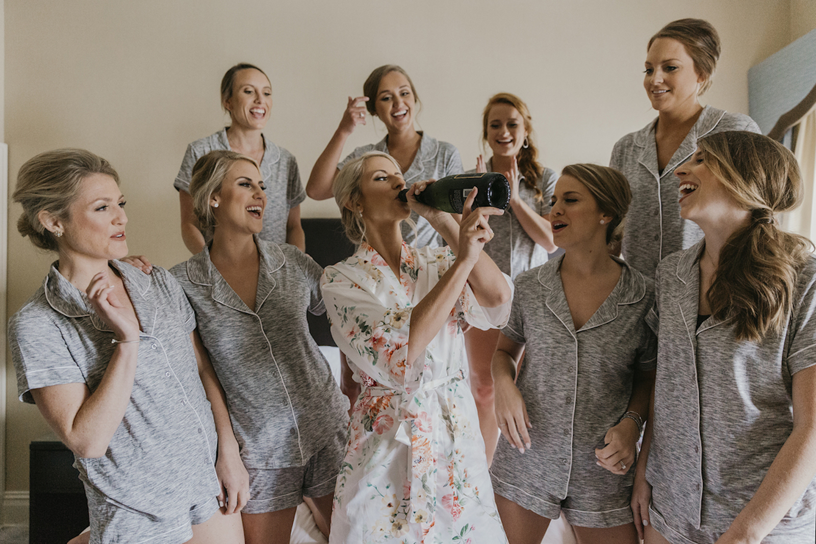 bride in floral robe drinking champagne surrounded by laughing bridesmaids in matching grey pajamas