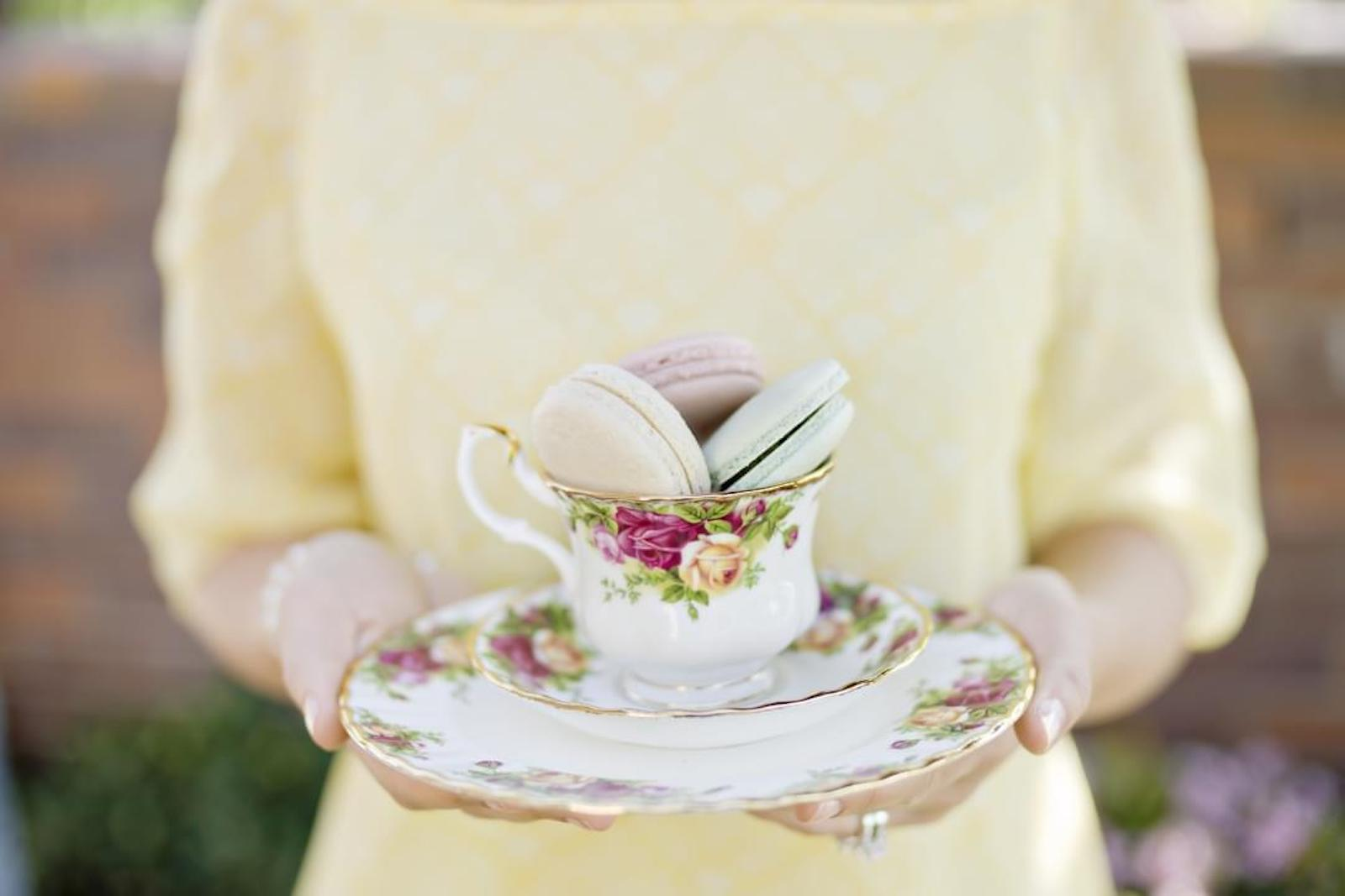 woman in yellow dress holding antique tea cup with macaroons inside