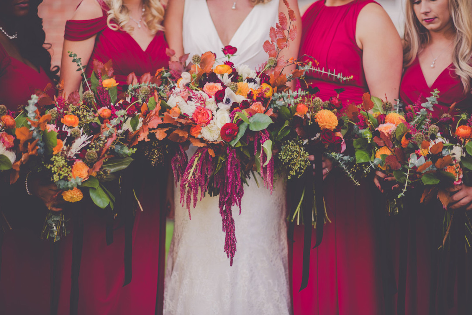 bride and bridesmaids from the neck down in fuchsia pink dresses holding bouquets of orange and pink flowers
