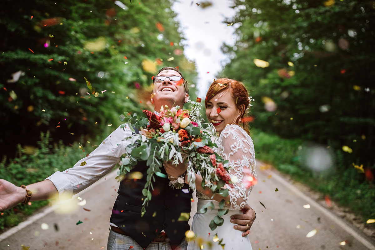 married couple enjoying colorful confetti during wedding