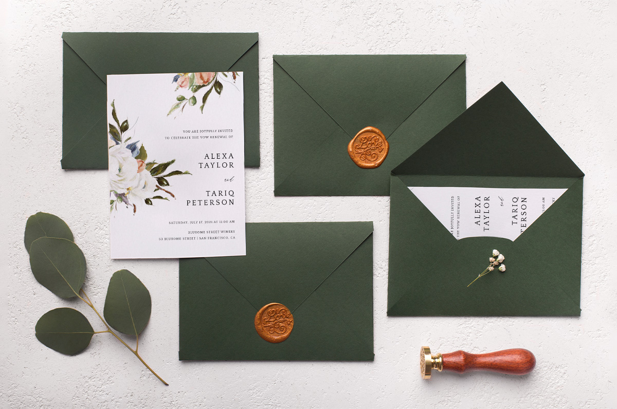 green invitation suite laying on beige table.