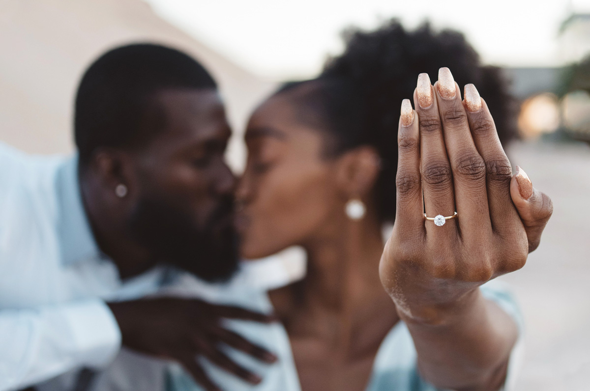 couple kissing showing off engagement ring.